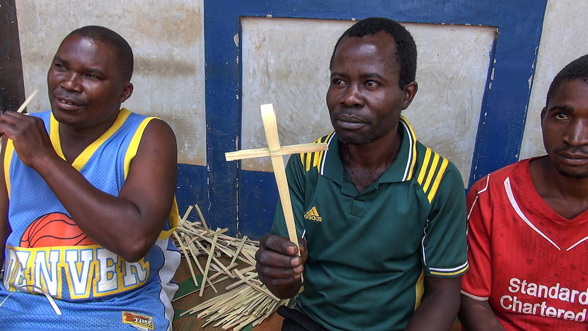 a man from Masasi Village at Tanzania holding a handwoven palm crosses after made it