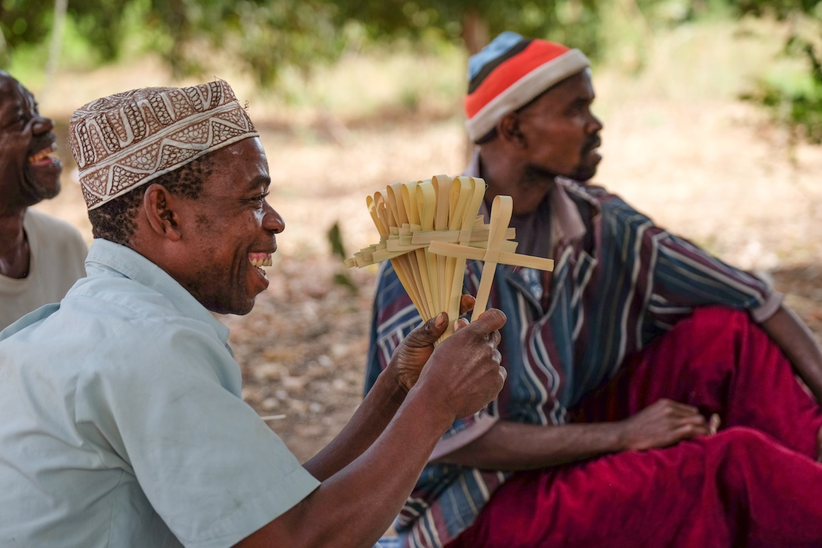 People from Tanzania making handwoven palm crosses