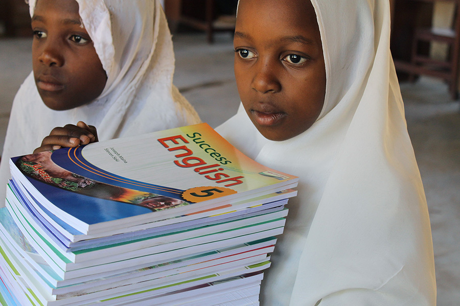 pupils of Mkuti primary holding books, project funded by African Palms selling palm crosses