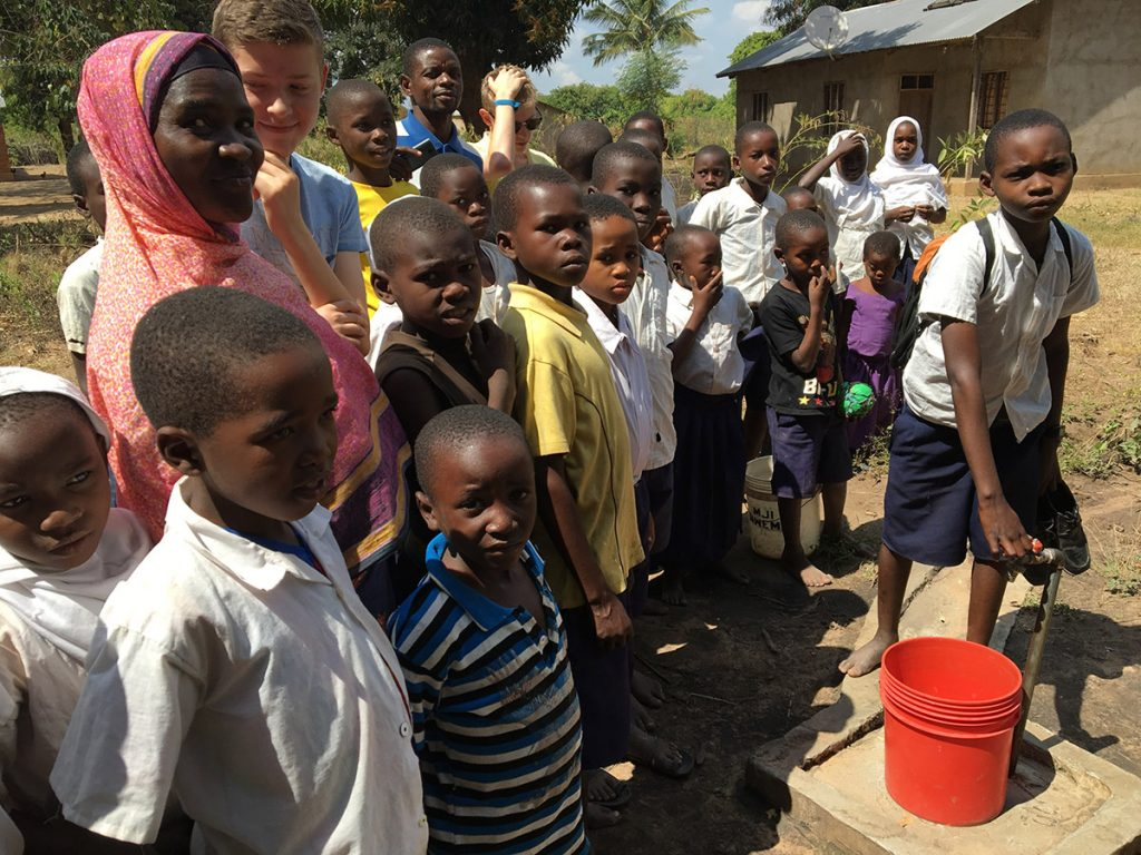 Local children at water point pipeline at Chipinpinbi project funded by African Palms selling palm crosses