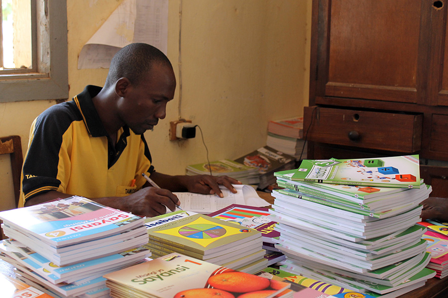 Officer Masasi recording books before distribution, project funded by African Palms selling palm crosses
